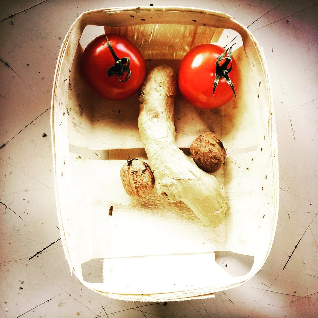 Zwei Tomaten, ein Ingwerstück und zwei Baumnüsse bilden, in einem rechteckigen Holzkörbchen ein Gesicht.