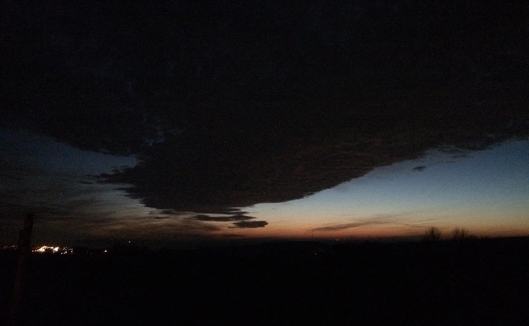 Fette schwarze Wolke über letzten hellen Himmelsflecken beim winterlichen Eindunkeln.
