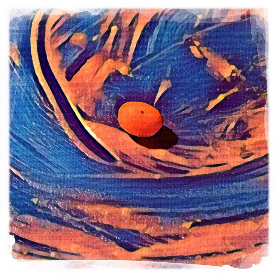Quadratisches, weiß gerahmtes abstraktes Bild. In der Mitte ein kleiner  runder orangefarbener Fleck, der Schatten wirft,  darum herum orangefarbene Schlieren auf mittelblauem Hintergrund.  (Das Originalbild zeigte einen leeren Teller mit Saucenresten und einem winzigen Kartöffelchen).